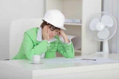 5814682-mujer-triste-el-ingeniero-con-un-casco-en-la-cabeza-se-sienta-en-una-mesa-en-un-lugar-de-trabajo